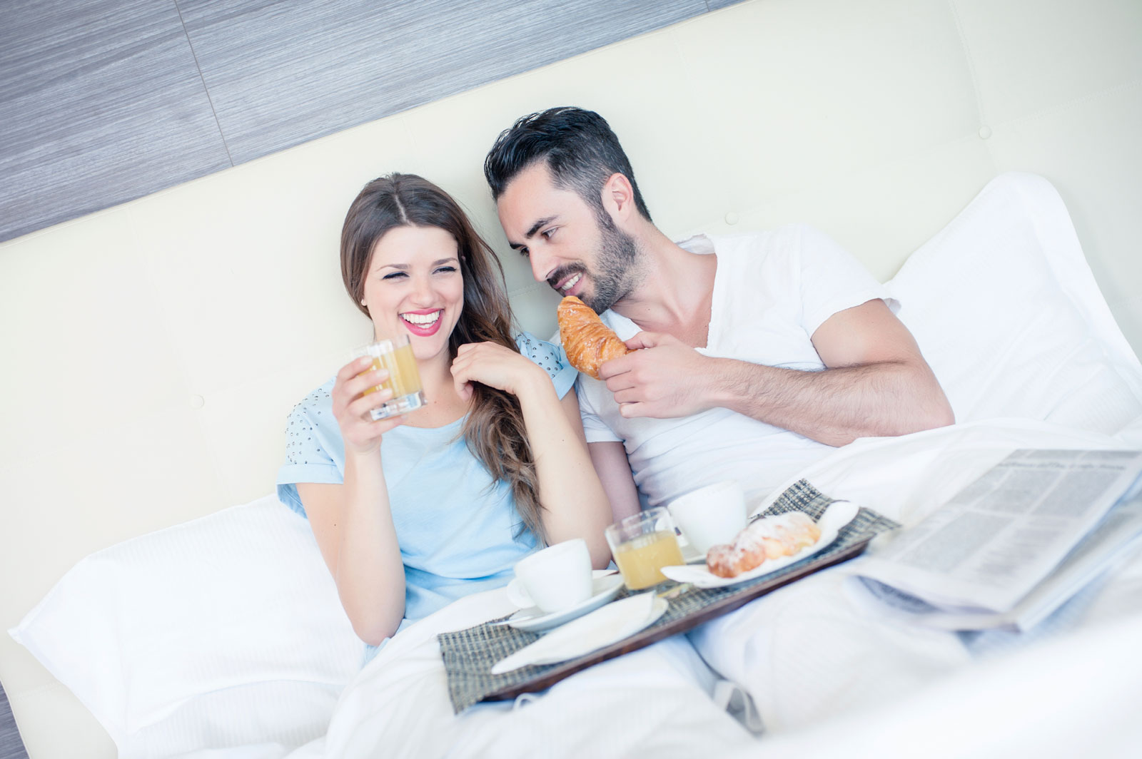 man and women eating break in bed