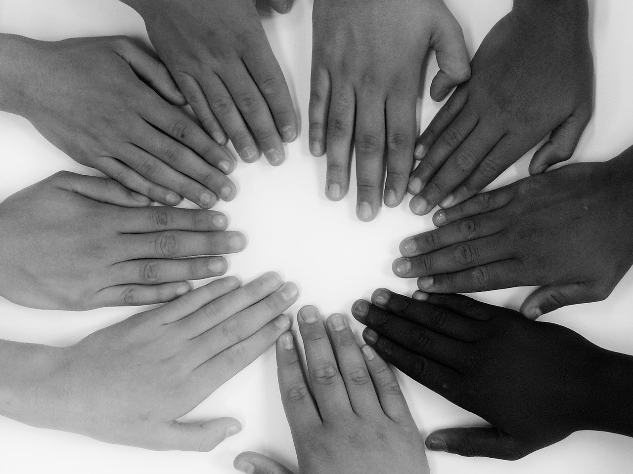 black and white photo of hands in a circle